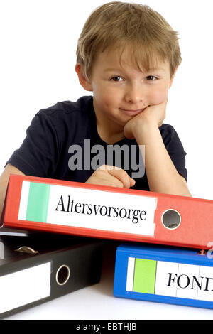 little boy smirking while leaning on a file with the inscription 'Altersvorsorge' ('retirement planning') - Stock Photo