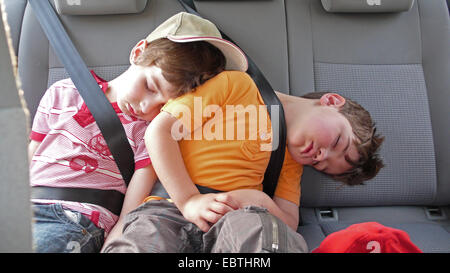 two belted little boys sleeping on the back seat of a car - Stock Photo