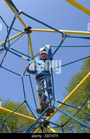 little boy on a climbing contraption on a playground - Stock Photo