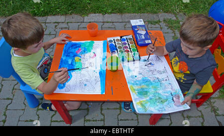 two children sitting in garden an painting with water colours - Stock Photo