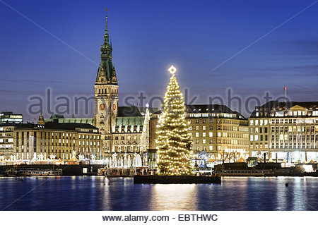 view over the Inner Alster Lake at the city centre in Christmas illumination with the town hall and a big Christmas - Stock Photo