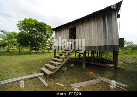 people sitting of a stairs infront of a little house of wood , Honduras, La Mosquitia, Las Marias - Stock Photo