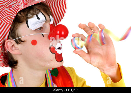 clown blowing in a paper streamer - Stock Photo