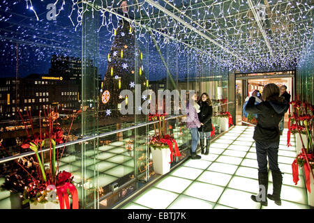 mother taking pictures of her two daughters in illuminated glass passage near Christmas market, Germany, North Rhine - Stock Photo