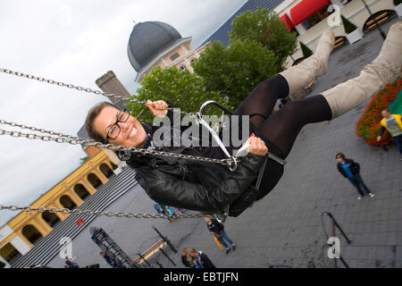 woman on a funfair ride, Germany, North Rhine-Westphalia, Bruehl - Stock Photo