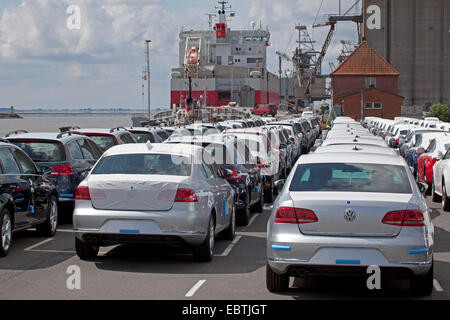 rows of new cars in front of car carrier Kess Isar Highway, Germany, Lower Saxony, East Frisia, Emden - Stock Photo