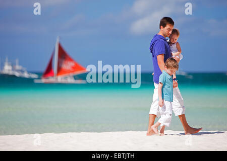 father walking with his to children on tropical beach, sailing boat in background - Stock Photo