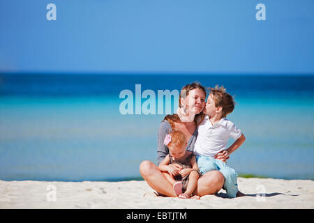 young woman sitting with her two little children on sandy beach - Stock Photo