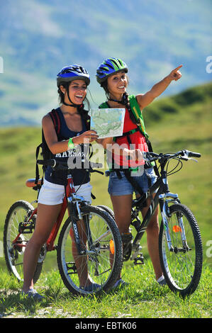 two teenage girls with mountain bikes looking for the right way, France, Savoie - Stock Photo