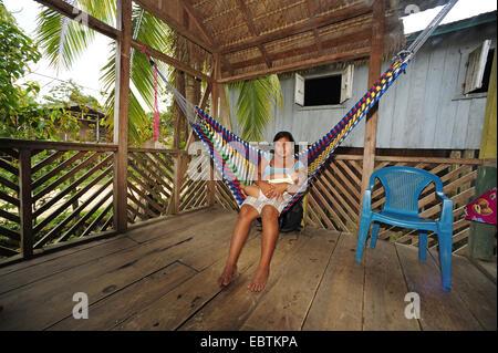 women with baby sitting in a hammock, Honduras, La Mosquitia, Las Marias, Brus Laguna - Stock Photo