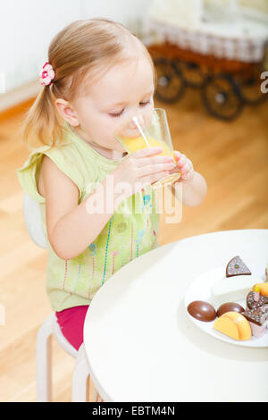 little girl sitting at the table drinking a glass of orange juice - Stock Photo