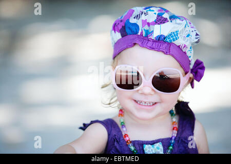 portrait of a little girl wearing sunglasses and fancy clothes - Stock Photo