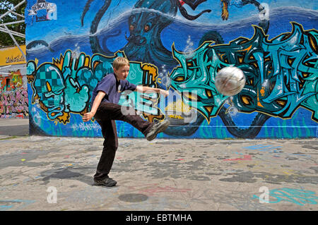 ten years old boy playing soccer in front of graffiti wall, Germany - Stock Photo