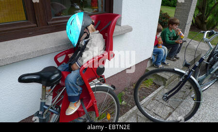 three little boys having returned from a bicycle tour: two drinking, one sleeping in the child seat on a bike - Stock Photo