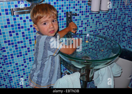 little Turkish boy in a bathroom washing his hands, Germany - Stock Photo