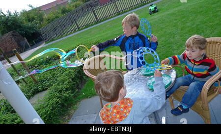 children in a garden making huge soap bubbles, Germany - Stock Photo