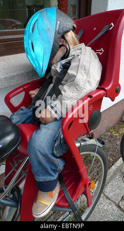 little boy having returned from a bicycle tour: two drinking, one sleeping in the child seat on a bike - Stock Photo