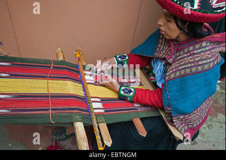 young woman in traditional dress working at a weaving loom at the local artisan workshop, Peru, Chincheros - Stock Photo