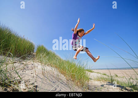 energetic boy jumping out of the dunes, Netherlands - Stock Photo