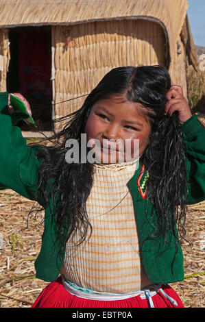 Quechua or Uros Indian girl on one of 42 floating islands on Lake Titicaca called 'Uros Islands', self-built of - Stock Photo