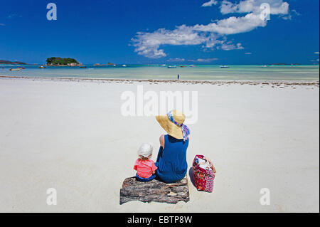 young mother and her adorable daughter enjoying a day at tropical beach - Stock Photo