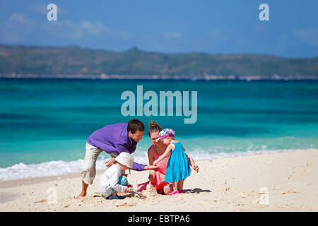 young family with two children playing on sandy beach - Stock Photo