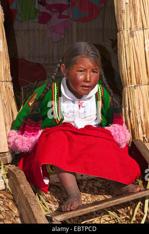 Uro girl sitting in the entrance of a hut on the floating Uros Islands, Peru, Lake Titicaca - Stock Photo