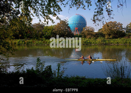 rowing boat on Rhine Herne Canal and gas container, Germany, North Rhine-Westphalia, Ruhr Area, Gelsenkirchen - Stock Photo