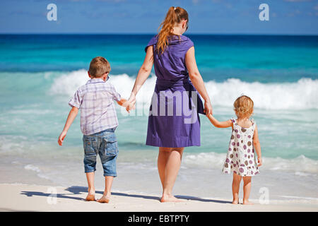 mother with two kids walking on tropical beach - Stock Photo