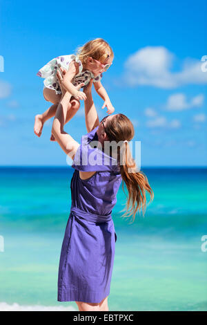 mother throwing her daughter in air at the beach - Stock Photo