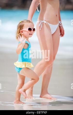 little girl next her mother on sandy beach - Stock Photo