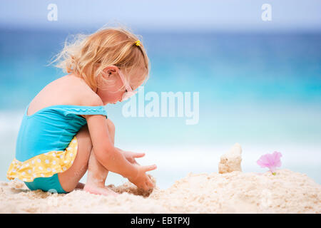 little blonde girl playing at tropical beach - Stock Photo