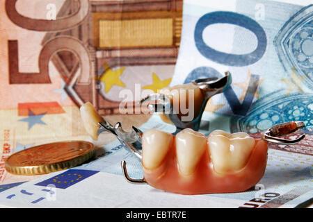 artificial dentures lying on Euro bills - Stock Photo
