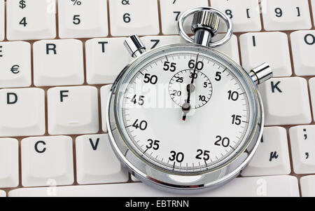 stopwatch on a computer keyboard - Stock Photo