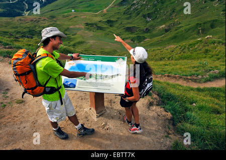 two wanderers orientating at a viewpoint indicator, France, Savoie, Vanoise National Park - Stock Photo
