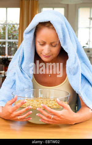 young woman with a cold is inhaling with camomile blossoms - Stock Photo