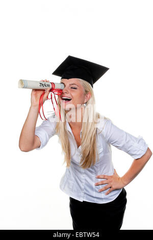 young woman wearing a graduation cap laughing while usig her rolled-up diploma as a telescope to look for a workplace - Stock Photo