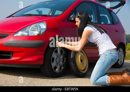 young woman having a tire failure with her car is changing a tire - Stock Photo