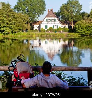 man with sleeping baby sitting on the lakefront, nature reserve Deipes Gatt, Germany, North Rhine-Westphalia, Ruhr - Stock Photo