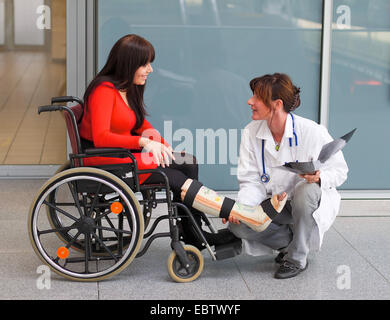 young woman with leg in plaster sitting in a wheel chair and talking to a doctor - Stock Photo