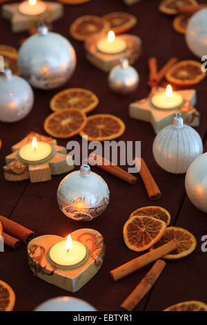 Christmas decoration with cinnamon sticks, orange disks and candles - Stock Photo