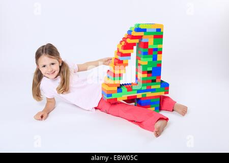 four-year-old girl with a large number '4' built of Lego bricks - Stock Photo
