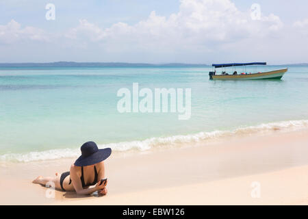 Woman looking at mobile phone on the beach, archipelago Bocas del Toro, Panama - Stock Photo