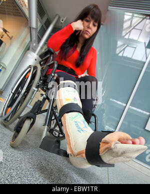 young woman with leg in plaster sitting in a wheel chair - Stock Photo