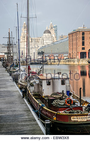 Boats moored at Albert Dock in Liverpool, UK, with the Liver Building in the distance - Stock Photo