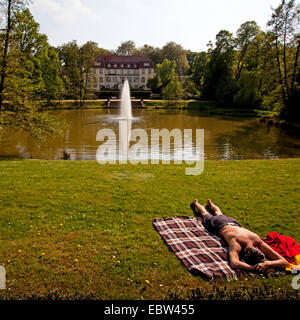 man lying on picnic rug in spa park of former solebar Raffelberg, Germany, North Rhine-Westphalia, Muelheim - Stock Photo