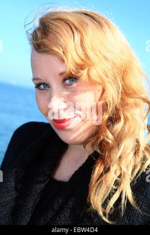 portrait of a young redheaded woman with freckles, Germany, Mecklenburg-Western Pomerania - Stock Photo