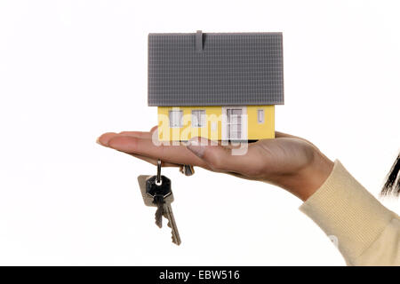 hand with miniatur model of a house and house keys - Stock Photo