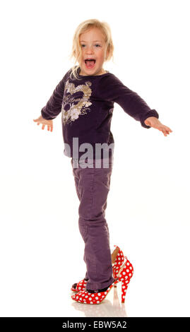 girl with big shoes, symbol for growth and future - Stock Photo