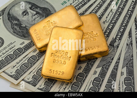 three gold bullion, 250 g Fine Gold, 999,9, on 100 dollar notes - Stock Photo